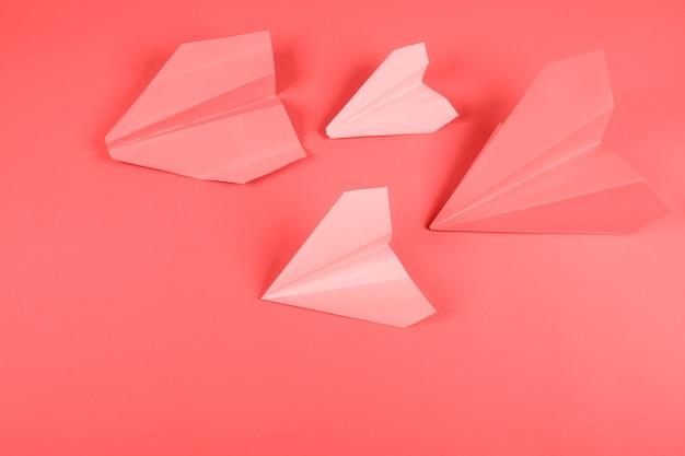 色付きの背景にサンゴとピンクの紙飛行機