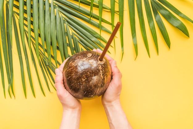 わらでココナッツの飲み物を持っている人