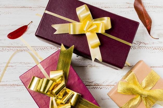 Крупным планом привлекательный подарок в штучной упаковке и листья на окрашенные деревянные доски