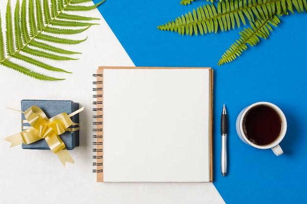 プレゼントボックススパイラルメモ帳。ペンと紅茶シダの葉のデュアル背景