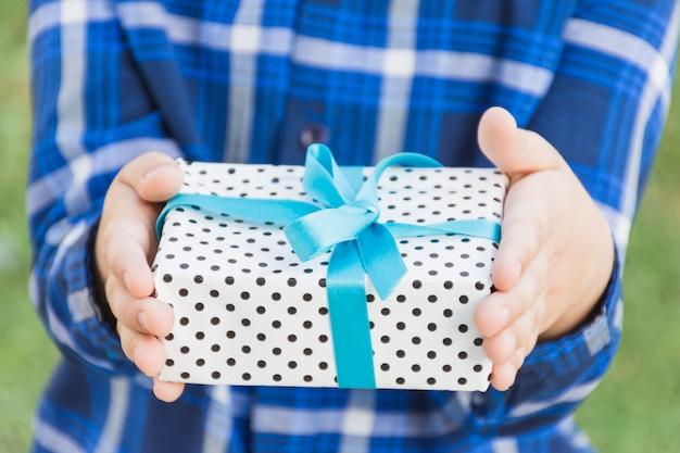 Средняя часть человека, держащего в руке подарочную коробку, перевязанную голубой лентой