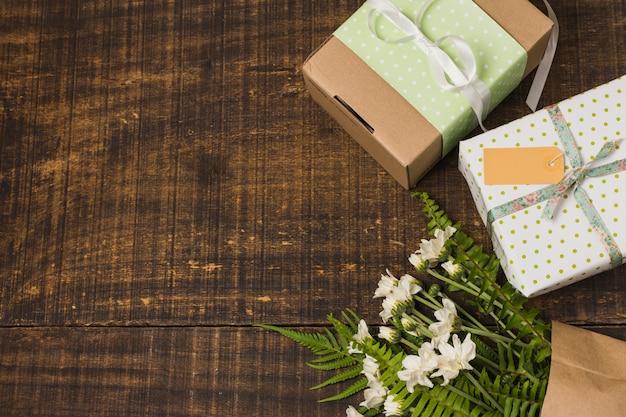 Букет цветов возле обернутых подарочных коробок на старом столе
