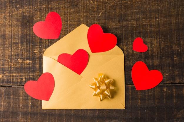 赤いハートと織り目加工の木の板の上の弓と黄色の開いた封筒