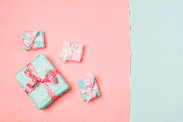Подарки украшены лентами, расположенными на двухцветной поверхности