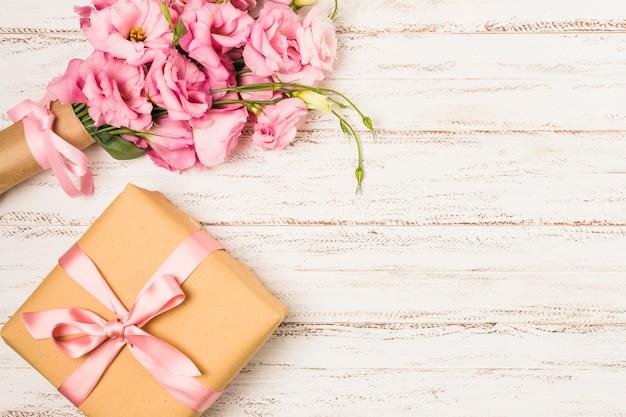 白の古いテーブルに包まれたピンクのトルコギキョウの花とギフトボックス