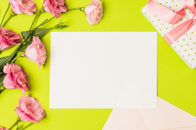 空白のグリーティングカード。明るい緑の背景の上のギフトとピンクのトルコギキョウの花