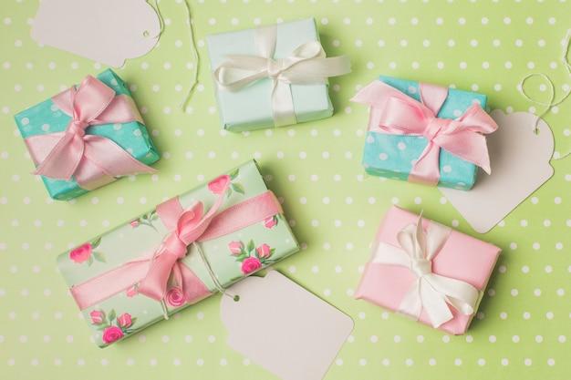 Подарочная коробка, завернутая в дизайнерскую бумагу с белой биркой на зеленой поверхности в горошек