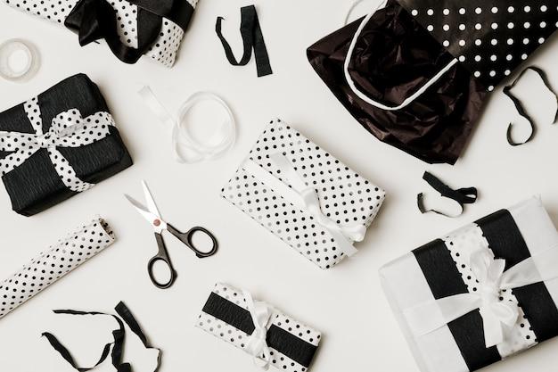 Вид сверху на подарочные коробки с дизайнерской бумагой; ножницы и бумажный пакет