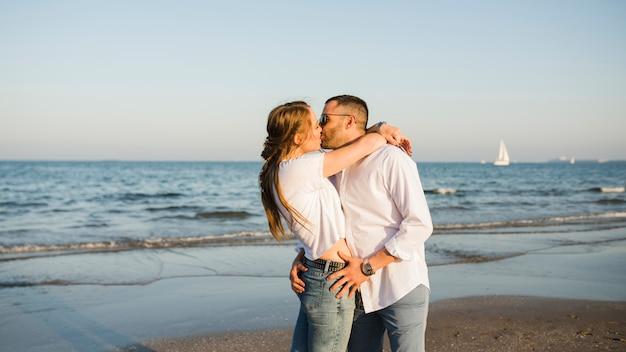Молодая пара целует друг друга возле моря на пляже