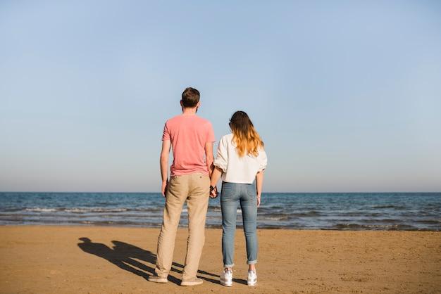 海を見てお互いの手を握って若いカップルの背面図