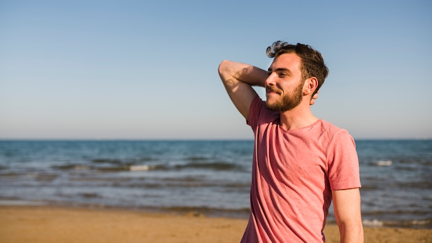青い空を背景にビーチに立っている若い男の側面図