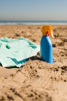 砂のビーチで毛布と日焼け止めクリームブルーのボトルのクローズアップ