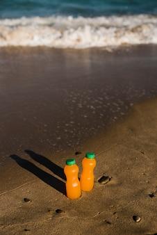Крупным планом двух бутылок апельсинового сока на берегу моря на пляже