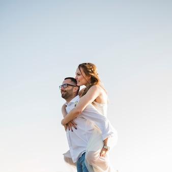 青い空を背景にビーチで彼の背中に彼のガールフレンドを運ぶ男
