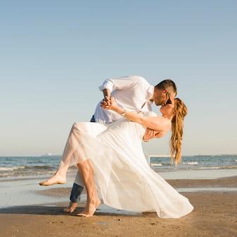ビーチでキスしながらポーズを与えるお互いの手を握って若いカップル