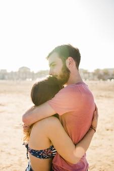 Молодая пара, обнимая друг друга на песчаном пляже в солнечный день