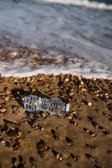 ビーチで海岸近くのプラスチック製の水のボトルを粉砕