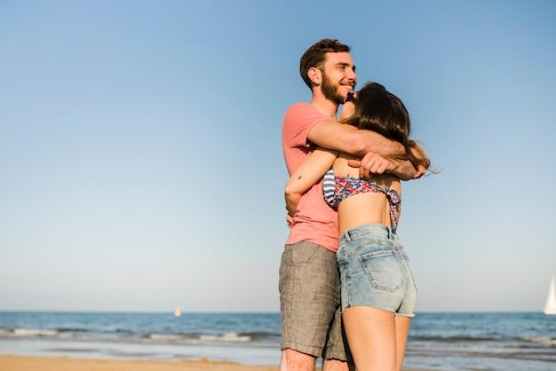 ビーチで海の前に幸せなロマンチックな若いカップルの立っています。