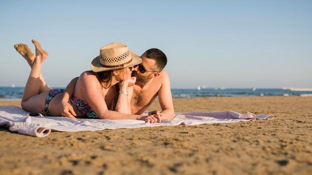 一緒にリラックスして夏のビーチで砂の上に横たわる若いカップルを愛する