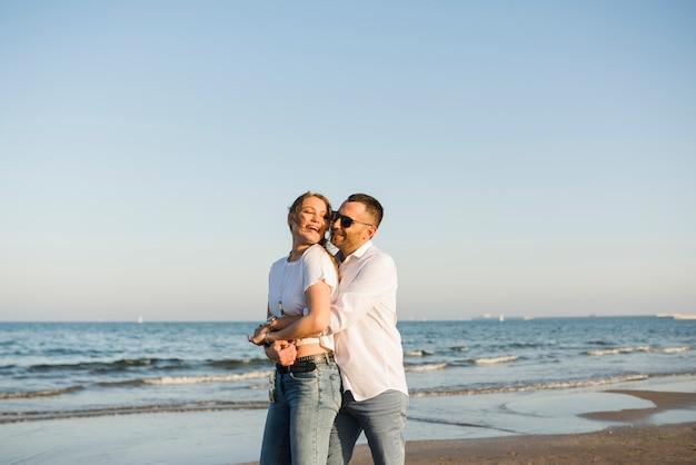 ビーチで青い空を背景に海の近くに立って後ろから彼のガールフレンドを抱きしめる男