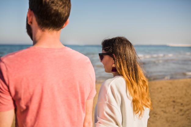 ビーチを歩いて若いカップルの背面図