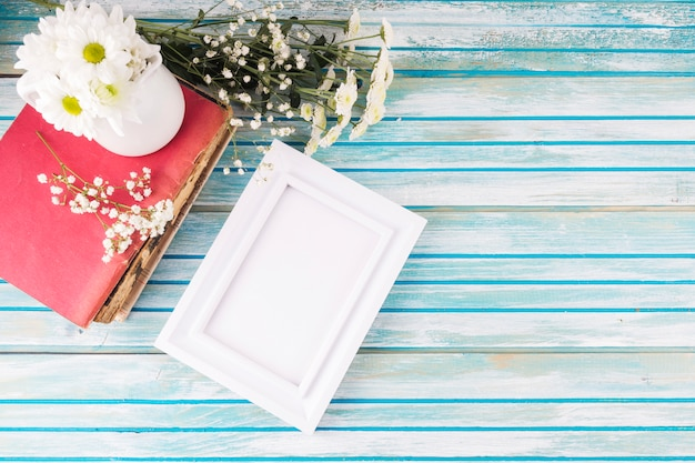 テーブルの上の空白のフレームとデイジーの花