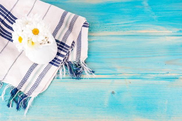 青いテーブルの上の水差しのデイジーの花