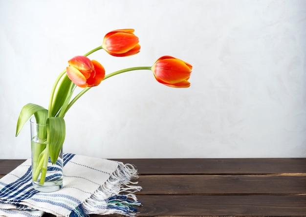 テーブルの上のガラスの花瓶に赤いチューリップ