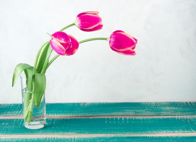 テーブルの上のガラスの花瓶にピンクのチューリップ