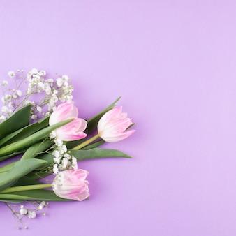 テーブルの上の枝を持つチューリップの花の花束