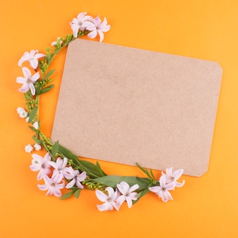 緑の葉と空白の紙と小さな花
