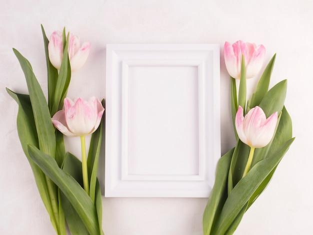 テーブルの上の空白のフレームとチューリップの花