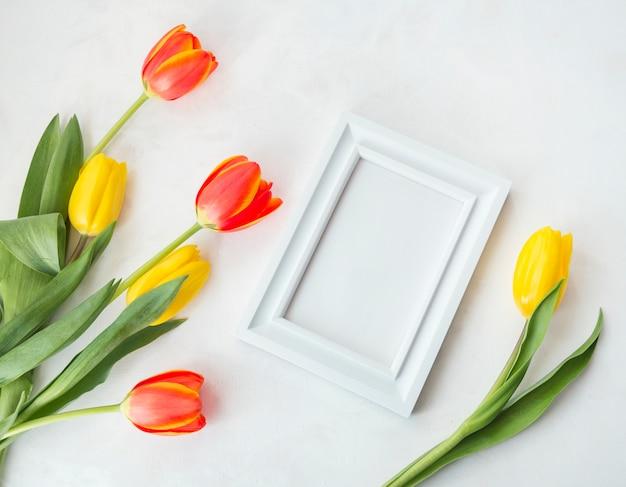 空のフレームと春の花を机の上に置く