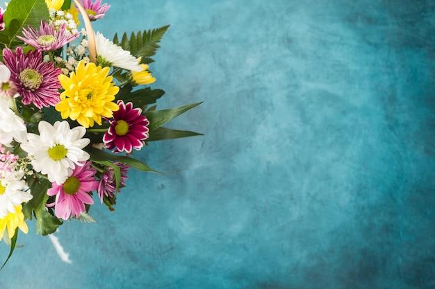 青いトーンの机の上に置かれた明るい花束