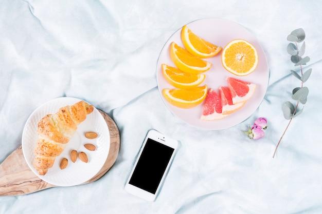 フルーツと携帯電話での朝食