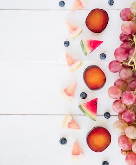 赤ブドウ;スイカの三角スライス。グレープフルーツとブルーベリーの木製の机の上