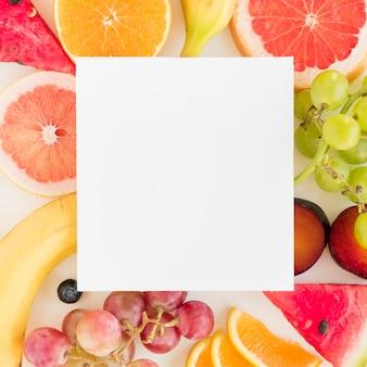 カラフルな柑橘系の果物の上の白い空白プラカード。ブドウとスイカ