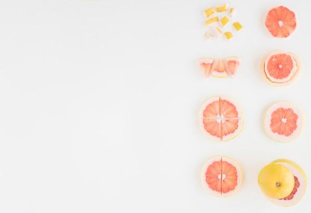 グレープフルーツの配置は、白い背景で隔離の異なるスライスにカット