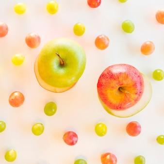 白地にブドウに囲まれた青と赤のリンゴのスライスを交換します。