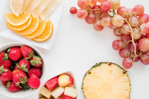 Ломтики цитрусовых фруктов; клубника; ананас; арбуз и виноград на белом фоне