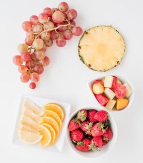 Фруктовые ломтики апельсина; лимон; арбуз; ананас; клубника и гроздь винограда на белом фоне