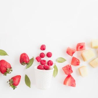 新鮮なラズベリーはイチゴで前面ガラスをこぼした。スイカとパイナップルの白い背景で隔離