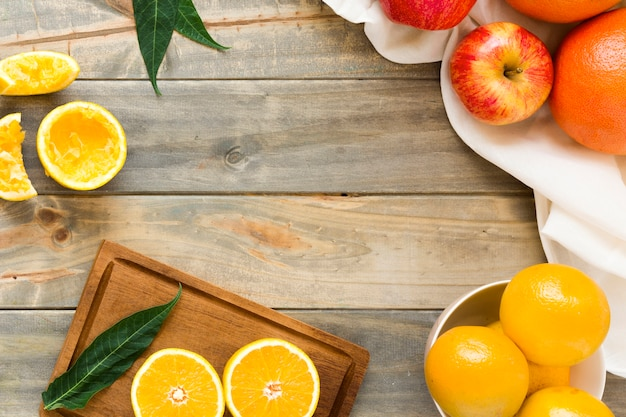全体と木製の机の上のリンゴとオレンジのスライス