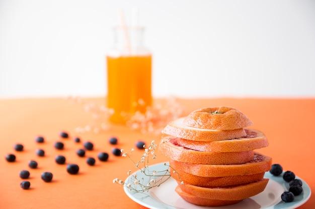 Спелый апельсин нарезать ломтиками с черникой и цветком гипсофилы на цветном фоне