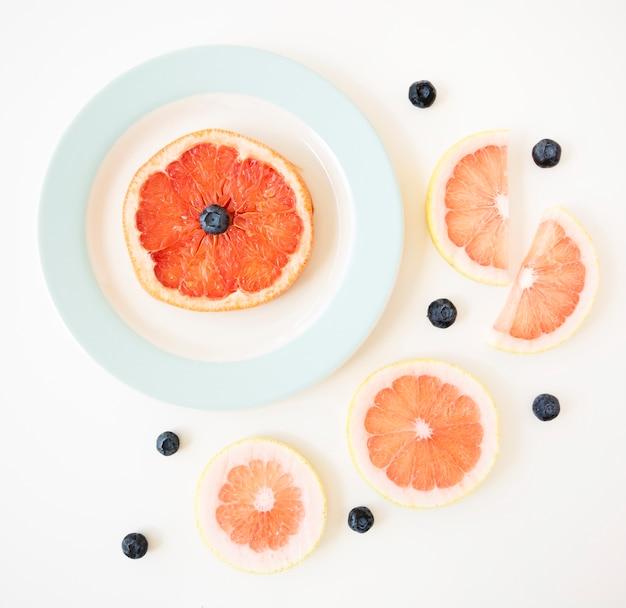 グレープフルーツのスライスと白い背景で隔離のブルーベリー