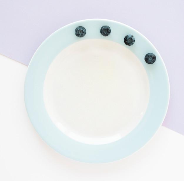 紫と白の背景にセラミック板の端にブルーベリー
