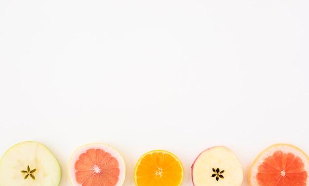 りんごのスライス。テキストを書くためのコピースペースと聖霊降臨祭の背景に分離されたグレープフルーツとオレンジスライス