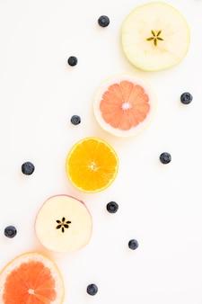 リンゴのスライスで飾られたブルーベリー。オレンジとグレープフルーツの白い背景で隔離
