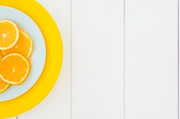 Поднятый вид апельсиновые дольки на белые и желтые тарелки на деревянной доске