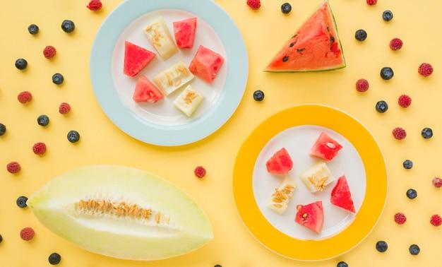 Кусочки дыни и арбуза на двух пластинках, украшенные черникой и малиной на желтом фоне